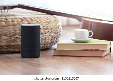 Personal assistant loudspeaker on a wooden floor of a smart home living room. Next, a guitar and some books and a cup of coffee. Copy space for Editor's text.