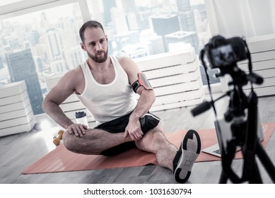 Personal blog. Confident appealing male blogger filming video while training and sitting near window