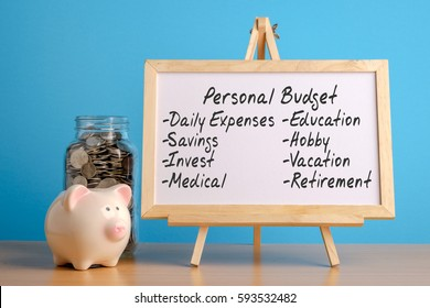Personal budget, financial concept. Mason jar with coins inside, piggy bank and whiteboard on wooden table.