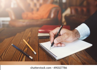 Personal and business correspondence. Unrecognizable man in suit writes text in notebook.