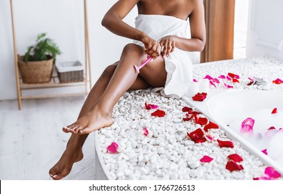 Personal care at home. African american girl in white towel shaves her legs, sitting in bathroom with foam and rose petals, cropped
