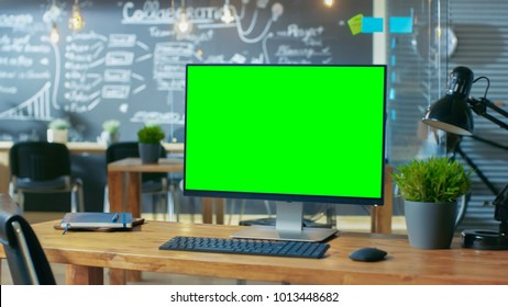 Personal Computer with Mock-up Green Screen Monitor Stands on the Office Desk, In the Background Man Works in the Creative Office at Daytime.