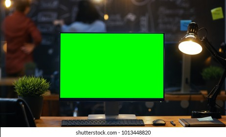 Personal Computer with Mock-up Green Screen Monitor Stands on the Office Desk, In the Background People Work on a Blackboard Wall in the Creative Office.