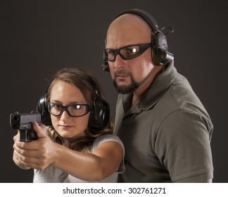 PERSONAL DEFENSE, GUN SAFETY | Young woman learning proper gun control and weapon safety with instructor, wearing safety glasses and ear protection.  Her finger is straight and off the trigger.