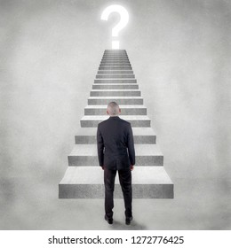 Personal development concept. Future success with risky challenge concept, rear view businessman facing question mark over the top of staircase ladder