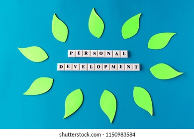 Personal development - text on plastic cubes with stickers on blue background. Business or education concept.