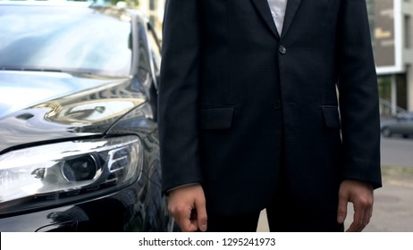 Personal driver standing near business class car waiting for vip passenger