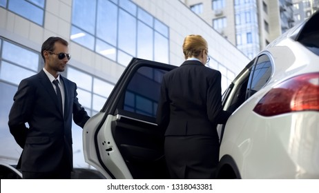 Personal driver waiting for boss on parking lot, helping her to get into car