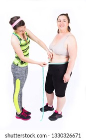 Personal female trainer is measuring the waist of a voluptuous woman,isolated o white.