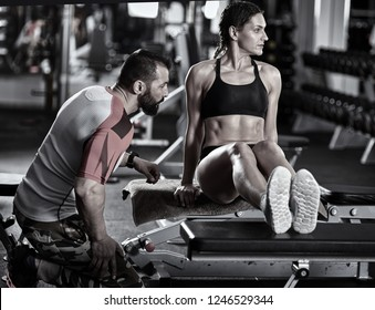 Personal fitness trainer assisting a young woman with workout