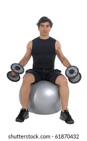 Personal fitness trainer (coach) sitting on a power ball exercising with dumbbells over white background