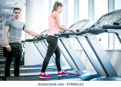 Personal fitness trainer watching his private client while walking on treadmill in modern fitness studio facility.