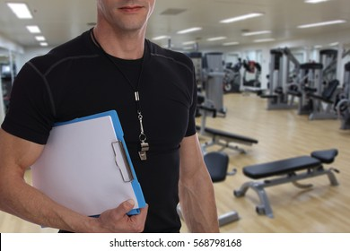 Personal fitness trainer with workout plan close up in gym background. Sport, fitness and healthy life style concept.