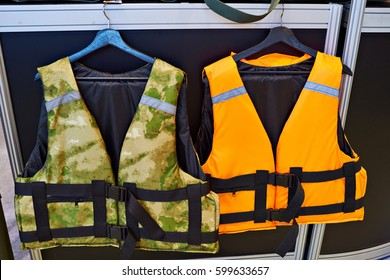 Personal flotation device as a life jacket in store. Orange and green