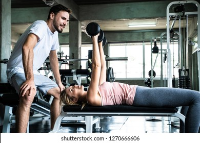 Personal instructor help young caucasian lifting dumbbell in factory gym