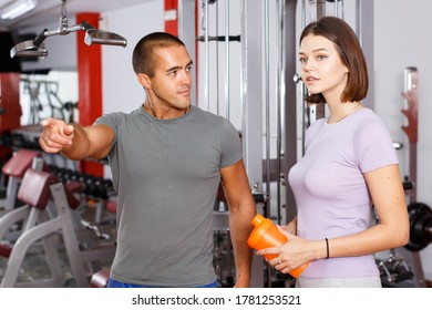 Personal instructor helping young woman with exercise technique at gym