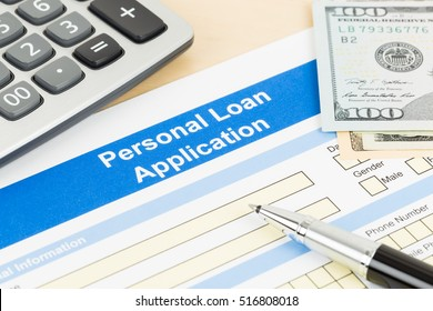 Personal loan application form with calculator, dollar money, and pen