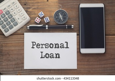 Personal Loan written on paper,Wooden background desk with calculator,dice,compass,smart phone and pen.Top view conceptual.