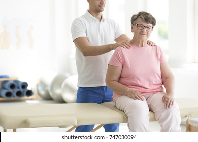 Personal masseur massaging senior woman sitting on massage bed in rehabilitation room