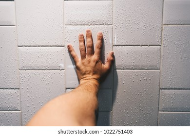 Personal perspective of hand grasping shower tiled wall