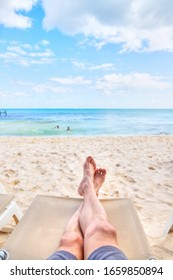 Personal perspective of man relaxing on a lounge chair at sandy beach with crossed legs view towards sea view and copy space. Shot taken in the Caribbean coast of Mexico at Cancun.