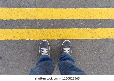 Personal perspective of person looking at his feet standing behind the street's yellow lines