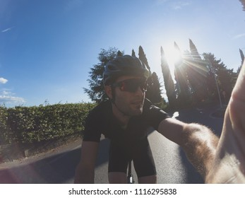 Personal perspective of a young adult cyclist training on a racing bicycle. Taking a selfie on a bicycle