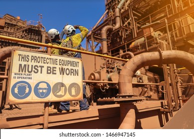 Personal protective equipment (PPE) must be worn sign with defocused of construction workers wearing white hard hat at the background while working on live refinery plant construction site Perth