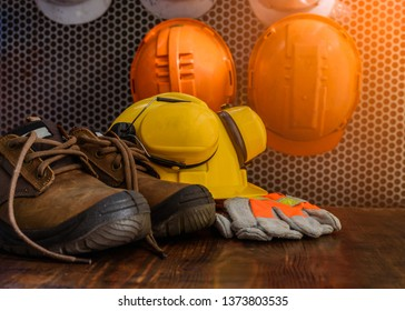 Personal protective equipment in the workplace is placed on a wooden table,with a safety helmets hanging in the background.