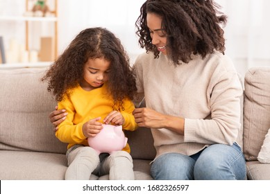 Personal Savings. Little African Girl Putting Money To Piggybank Sitting With Mother On Couch Indoor