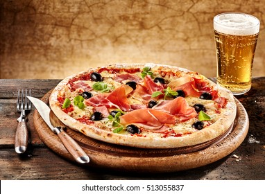 Personal serving of bacon pizza with beer beside knife and fork on round wooden plate