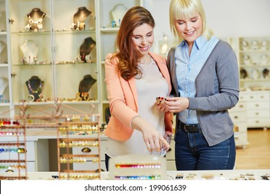 Personal Shopper advising woman in jewelry store while buying a bracelet
