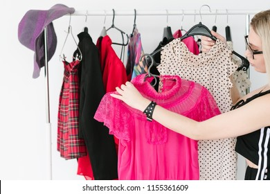 personal style consultant or fashion stylist choosing trendy clothing for her client. woman holding two tops on hangers.