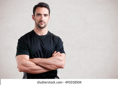 Personal trainer with is arms crossed, isolated in grey