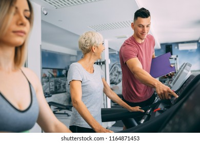 Personal trainer assist senior woman exercising on trademill machine at gym.