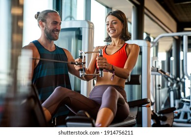 Personal trainer assisting woman to lose weight in gym