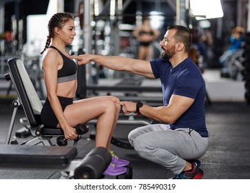Personal trainer assisting young woman in the gym