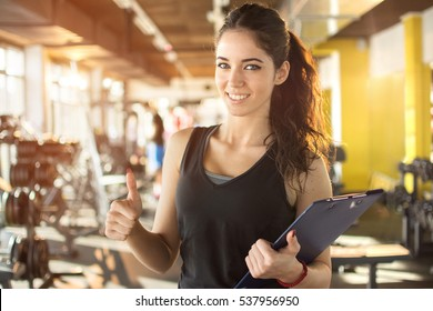 Personal trainer with clipboard showing thumbs up in gym.
