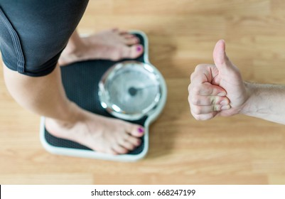 Personal trainer or coach giving thumbs up to a person standing on scale. Success and great achievement in weight loss. Encouragement and motivation. Happy and satisfied with the results.