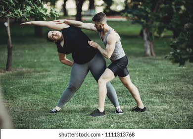 Personal trainer correct his client while doing yoga exercise. Overweight woman stretching muscles with instructor support.