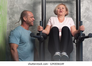 Personal trainer demonstrates how to properly to do the exercises in the simulator for middle-aged woman in the gym. The concept of physical activity in the elderly