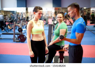 Personal trainer demonstrating a bicep exercise. At the gym. Selective focus.