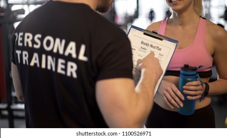 Personal trainer discussing weekly meal plan with female client in gym, support