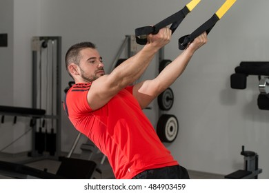 Personal Trainer Does Crossfit With Trx Fitness Straps In The Gym's Studio