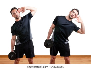 Personal Trainer doing dumbbell side bends for training his abs, in a gym