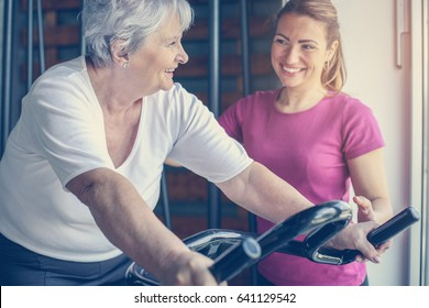 Personal trainer exercise helps senior woman. Senior woman on the elliptical machine.