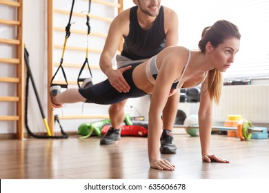 Personal trainer and fit woman doing plank exercise