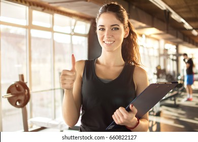 Personal trainer or fitness instructor holding a clipboard and showing thumbs up in gym.