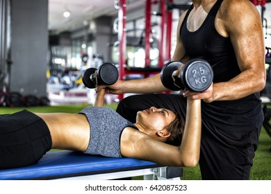 Personal trainer with girl on training use dumbbell workout in fitness center