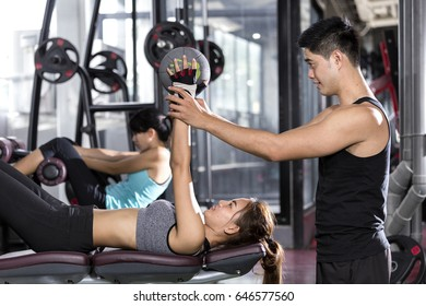 Personal trainer with girl on training Weight lifting ball workout in fitness center.